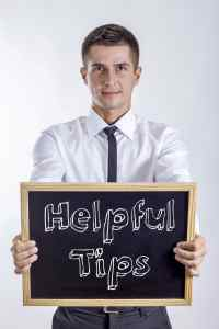 Helpful Tips - Young businessman holding chalkboard with text
