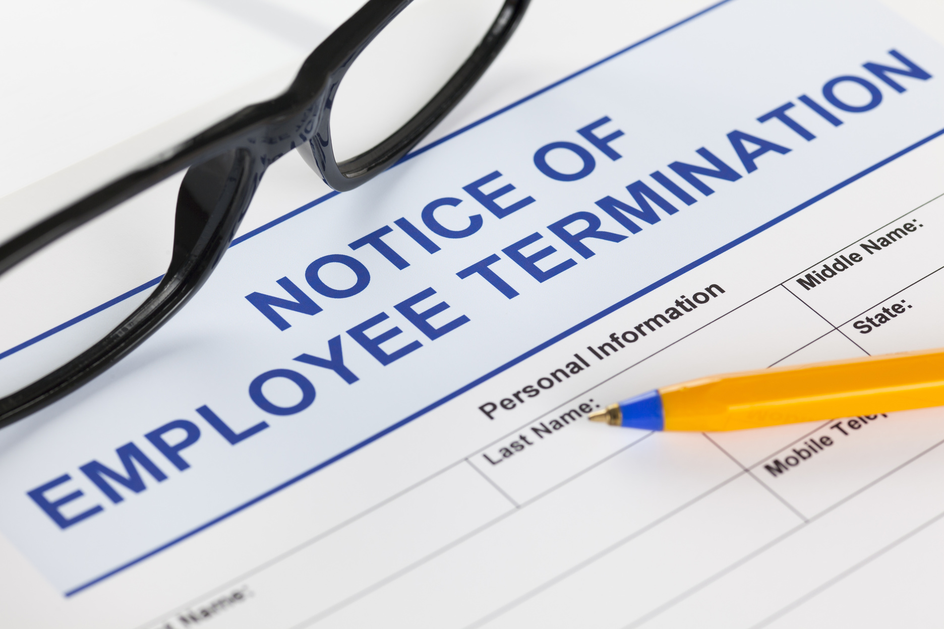 Notice of employee termination with glasses and ballpoint pen.