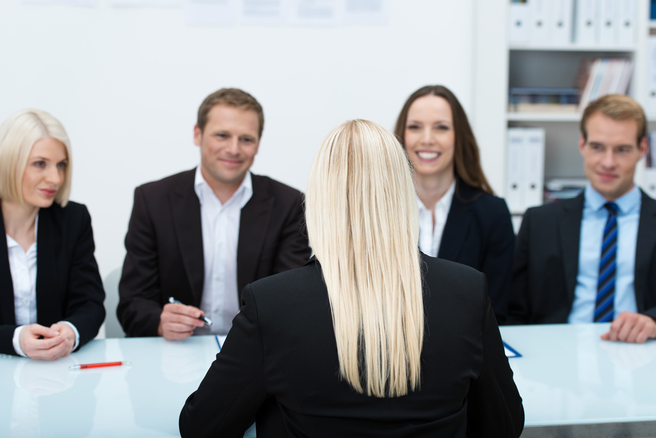 Young female job applicant in an interview sitting with her back to the camera facing a row of personnel executives